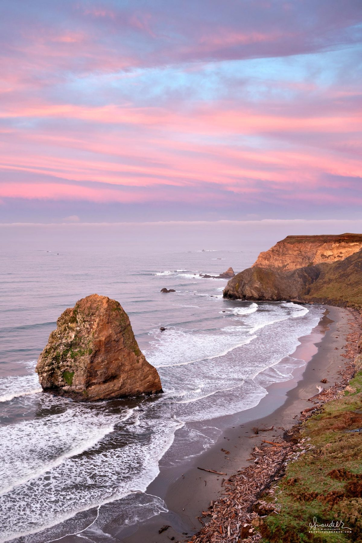 Dawn skies brings pink light to Cape Blanco and Needle Rock. Cape Blanco State Park, Curry County, Oregon South Coast landscape photography.