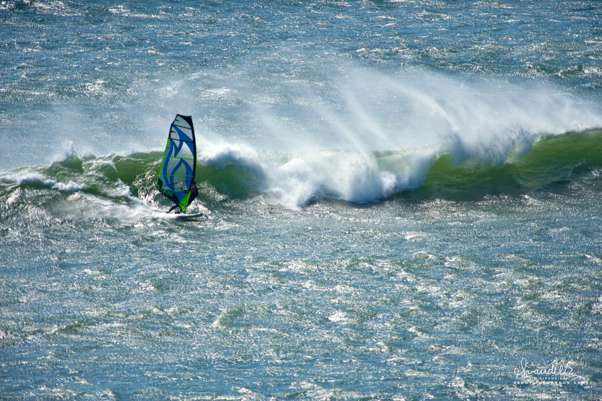 A windsurfer rides the wild waves off Cape Blanco's south point. Cape Blanco State Park, Curry County, Oregon South Coast.