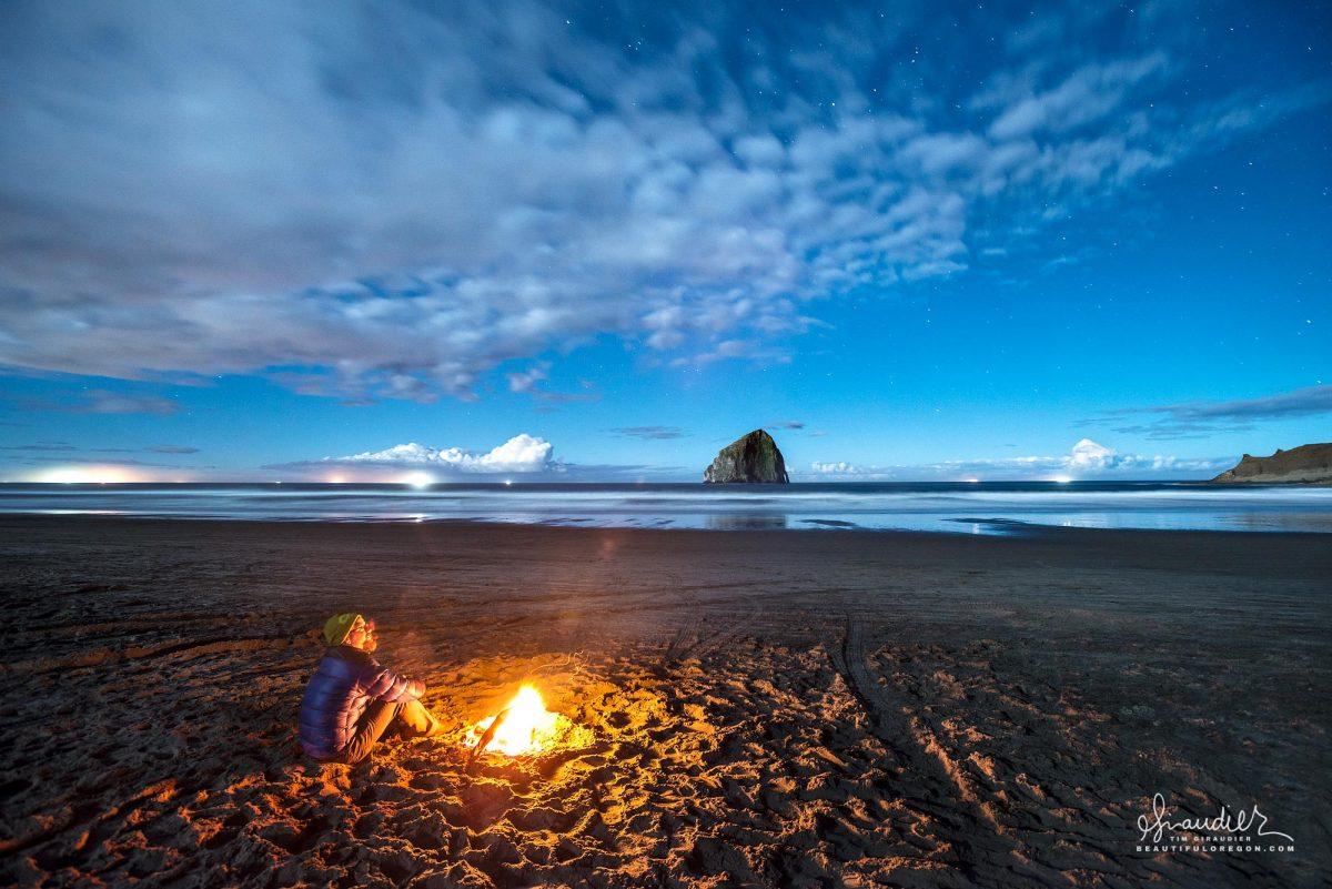 Cape Kiwanda beach campfire in march. Overhead a starry sky, offshore crab boats set pots beneath moon lit thunderclouds. Pacific City ,Oregon Coast