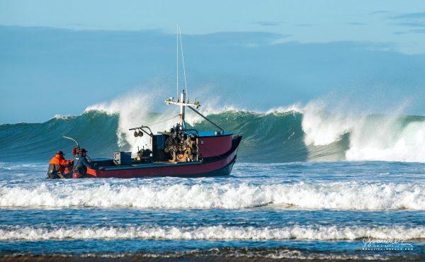 Pacific City dorymen launch their fishing boat through the breakers at Cape Kiwanda. Tillamook County, Oregon North coast photography.