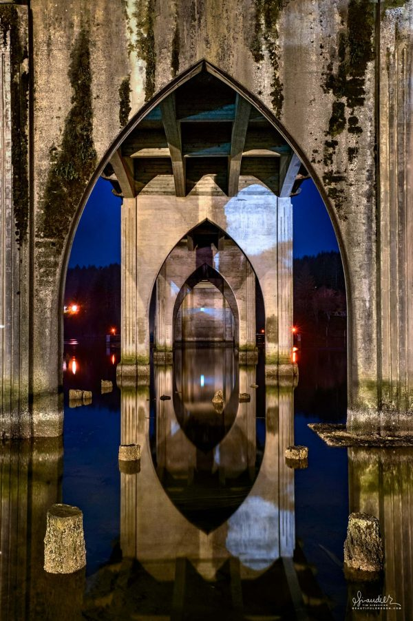 Arched buttress supports and reflections below U.S. Highway 101 Siuslaw River Bridge. Lane County, Florence Oregon Central Coast.