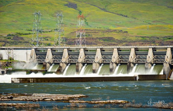 The Dallas Dam spills spring snow melt over its flood gates on the Columbia River. Wasco County, Oregon.