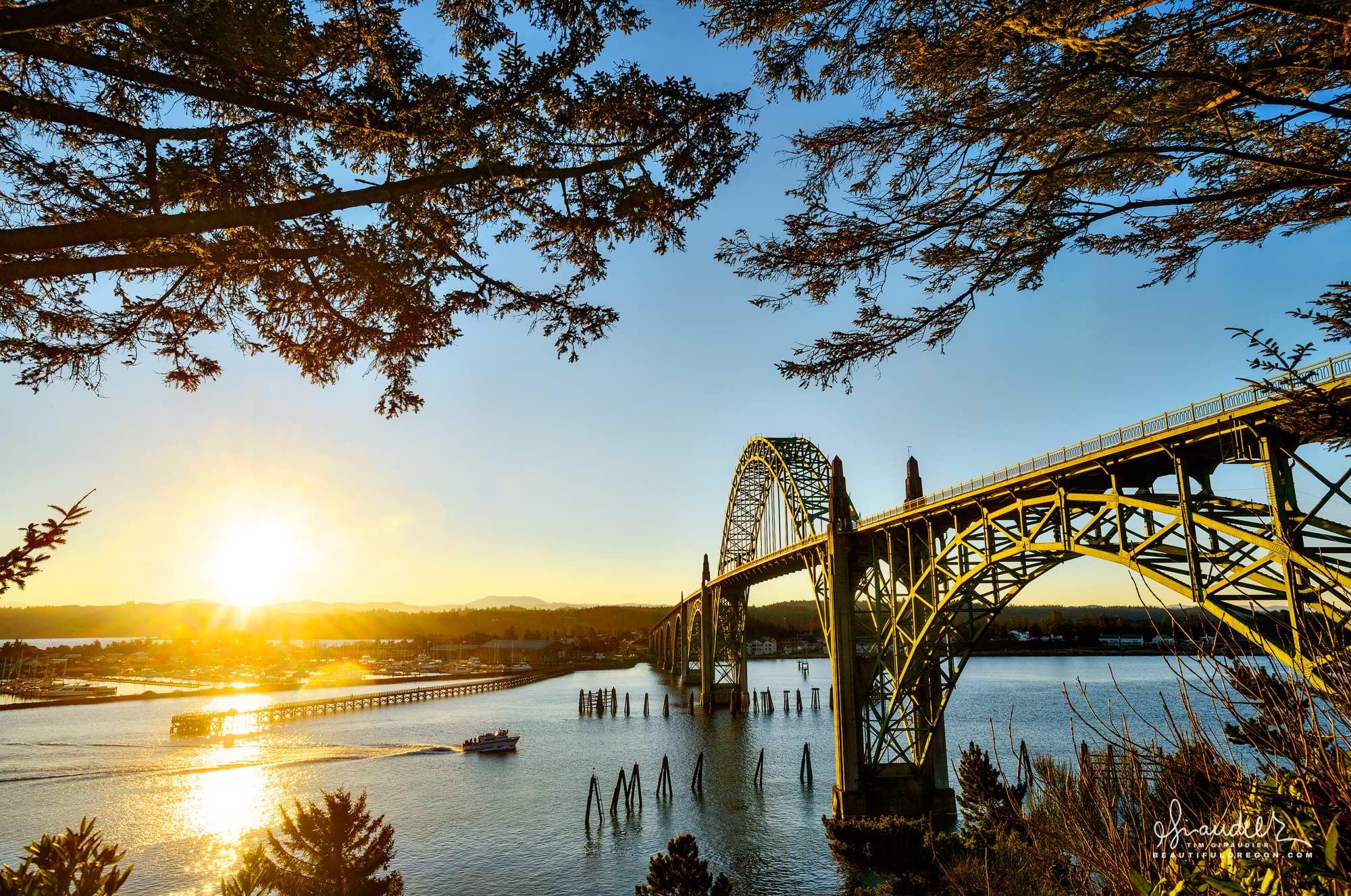 A charter boat heads to sea beneath the Yaquina Bay Bridge at sunrise. Lincoln County, Newport, Oregon Central Coast.