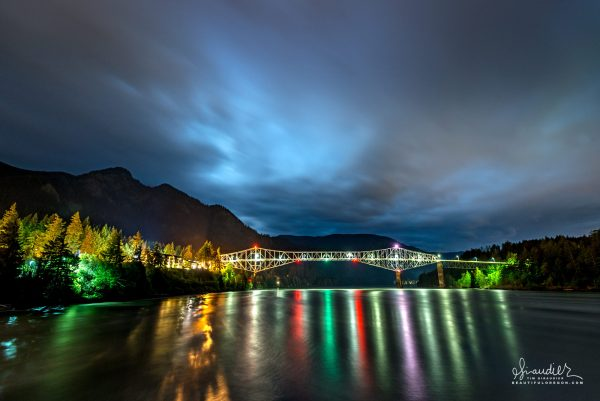 A stormy night sky over Bridge of the Gods and the Columbia River. Photographed from Thunder Rock Island and the community of Cascade Locks. Hood River County, Columbia Gorge, Oregon.
