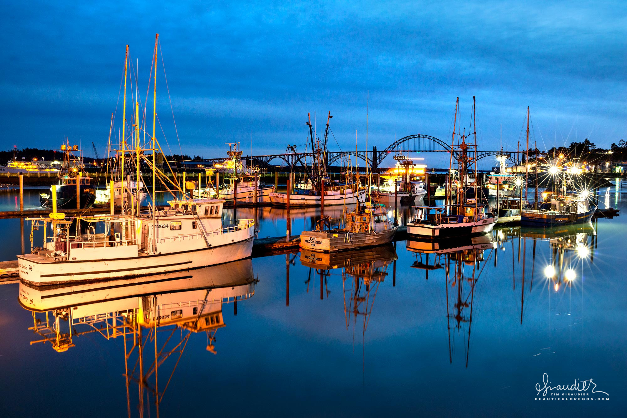 In the early morning hours, commercial fishing boats prepare to head to sea and collect their crab pots. Yaquina Bay, Newport Oregon.