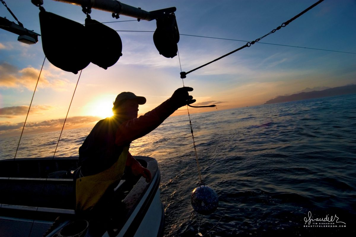 A commercial salmon fisherman brings in a canon ball down rigger as he pulls gear at sunset. Cross Sound, Southeast Alaska.