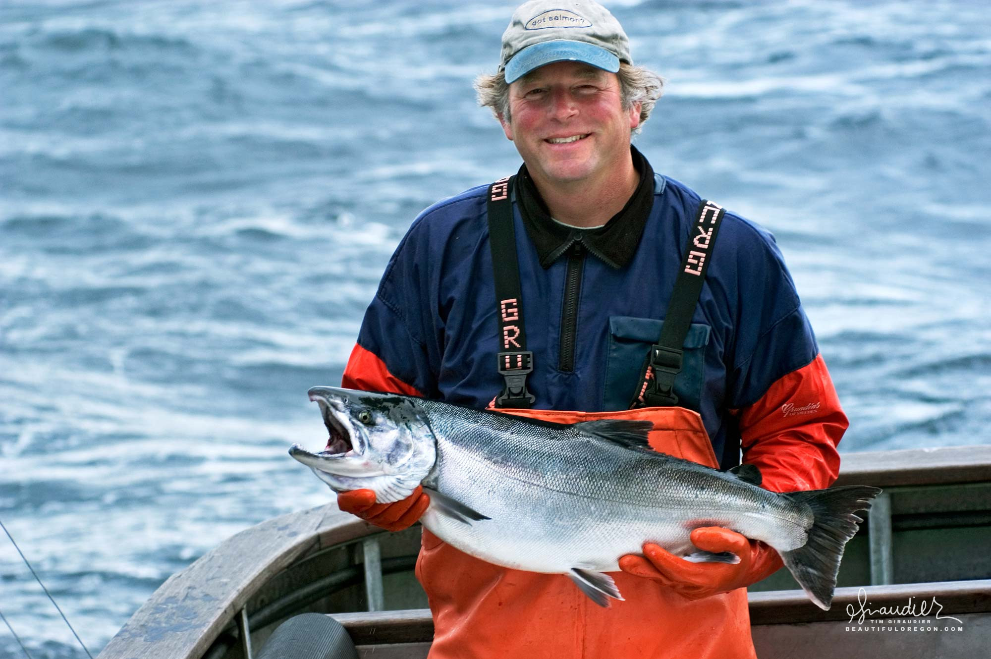 Rick Oltman, owner operator of F/V Cape Cleare Fisheries holds a late season silver salmon in the Gulf of Alaska. Commercial salmon troll fishery.