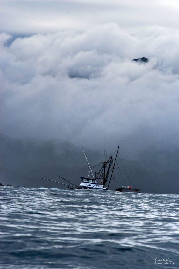 Beneath stormy skies, a steel boat trolls for King Salmon off Yakobi Island. Gulf of Alaska, Southeast Alaska.