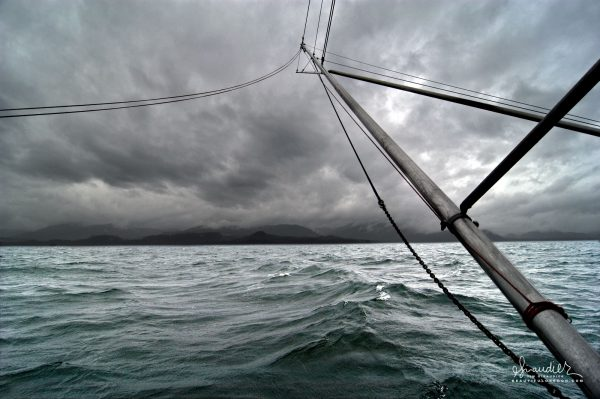 Stormy Skies Over Trolling Pole and Stabilizer Chain, an Alaskan salmon troller heads west in search of fish.