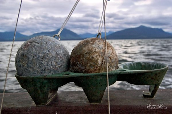 Cannonball downriggers neatly stowed and ready to fish, the Cape Cleare running east in search of fish. Commercial fishing southeast Alaska.