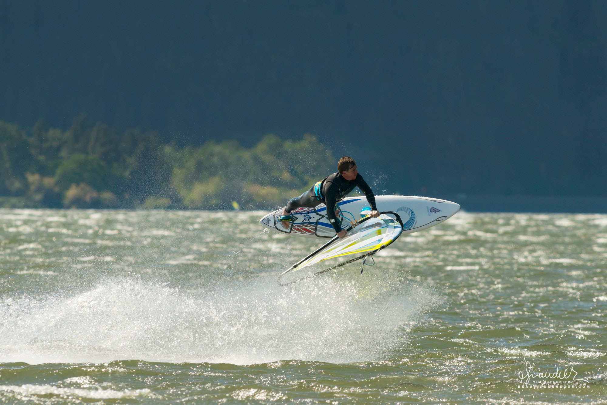 A windsurfer flies above the spray on a windy day in the Columbia River Gorge. Klickitat County, Washington State outdoor recreation.